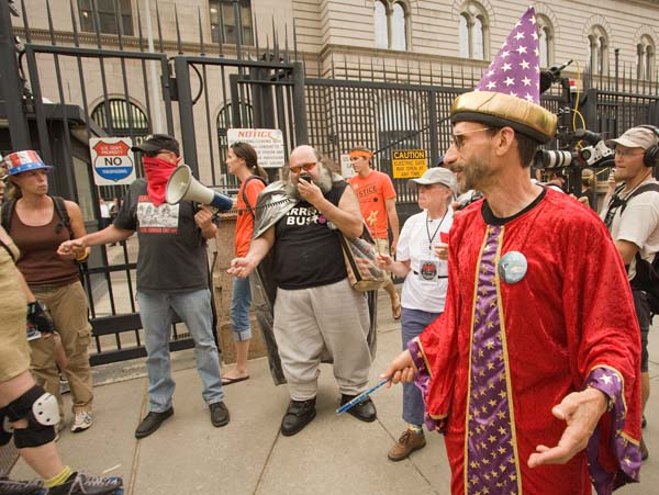"Mark Cohen of Recreate 68 leads the Shake Your Mint event. ""It's time to redistribute the wealth. (We'll) use our collective power to raise the mint building in the air and shake the money out of it for the people. Bring noise makers, energy, spells, magic, costumes, anything that gives you power."""