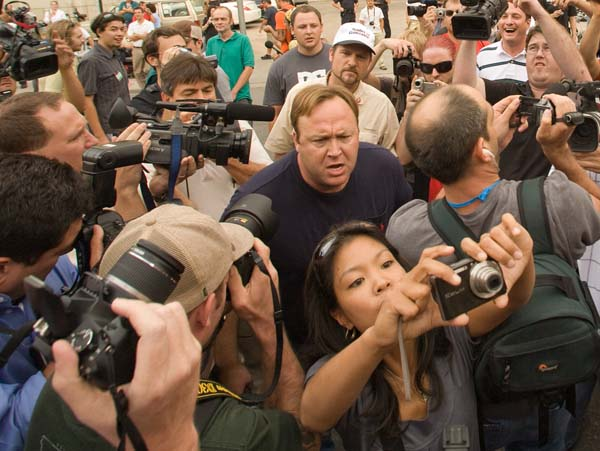 "Malkin repeatedly tried to carry on doing her job. Here she is holding her arms up to take photos of Pieman and the grandiose wizard. Jones would not let her have any peace and repeatedly came after her, like a junkyard dog. I heard him screech ""You're a monster! You want all these people put in torture camps!"" and something about ""Dick Cheney is getting ready to sink our own war ships!"" ""Shame on Michelle Malkin! She's a fascist piece of trash!"" When he was not abusing her, he was inciting the mob of journalists and journalist wannabe moonbatas with exhortations like ""Look! It's Michelle Malkin! Hey, everybody, come here, it's Michelle Malkin! She supports torture and wants to put everyone in internment camps!"" These quotes are from memory and not verbatim. His statements had some significance to me because of an interview he gave on radio. A couple of weeks ago, four a.m. couldn't sleep, hit the radio button, and I heard Alex Jones interviewed on Coast to Coast with George Noury. He was saying the most bizarre things about the U.S. government having established internment camps for millions of Americans here on the U.S. mainland. We are searching for the audio and will try to transcribe."